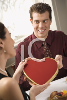Royalty Free Photo of a Man Giving a Heart Shaped Box of Chocolates to a Woman at a Restaurant