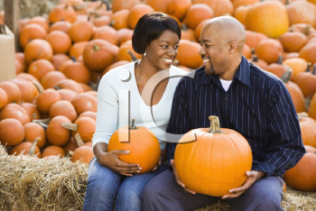 Royalty Free Photo of a Smiling Couple Sitting on Hay Bales and Holding Pumpkins at an Outdoor Market