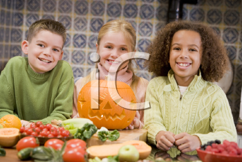 Royalty Free Photo of Three Children With a Jack-o-Lantern