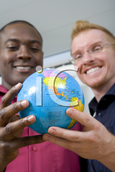 Royalty Free Photo of a Two Multi-Racial Men Holding a Small Globe