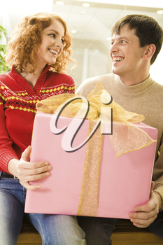 Portrait of smiling couple holding big pink gift box and looking at each other
