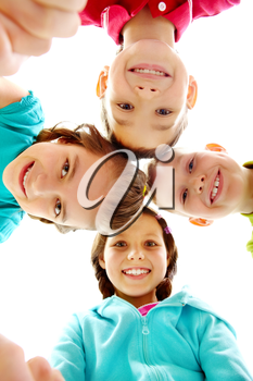 Company of four joyful children looking at camera