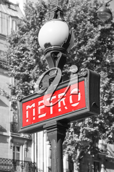 Street sign at the entrance to the Paris Metro, red banner on the street lamp, tonal correction effect