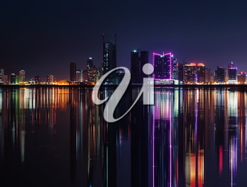 Night modern city skyline with shining neon lights and reflection in the water. Manama, the Capital of Bahrain, Middle East