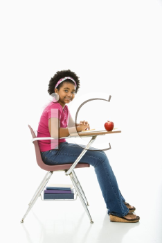 Royalty Free Photo of a Girl Sitting in a School Desk Smiling