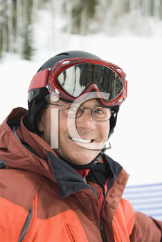 Smiling male skier wearing red goggles and orange ski jacket. Vertical shot.