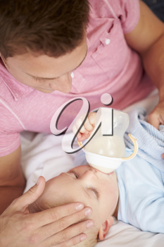 Father Giving Baby Son Bottle Of Milk
