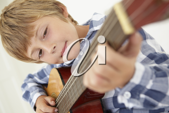 Young boy playing acoustic guitar