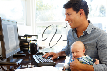 Father working in home office with baby