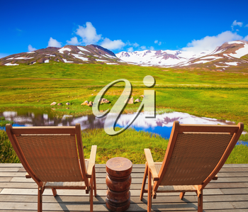Summer Iceland. Small lake surrounded by green meadow. At the lake on wooden platform there are two deckchairs