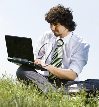 Portrait of young businessman doing computer work in the park