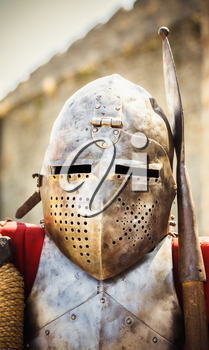 Medieval knight in helmet on ancient wall background