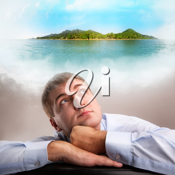 Tired office worker daydreaming about tropical vacation